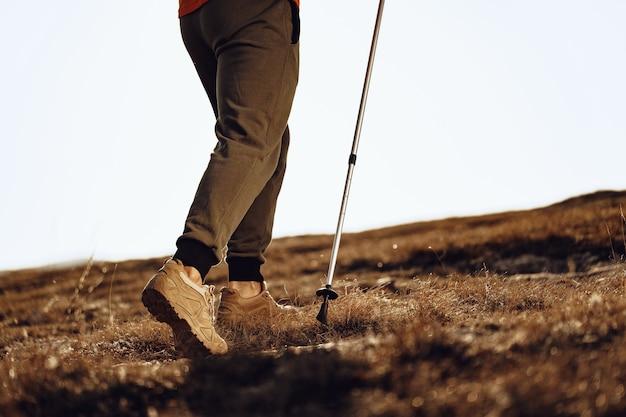 Путешественник человек с треккинговыми палками поднимается на гору