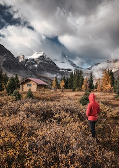 Man traveler with wooden huts in autumn forest at assiniboine provincial park