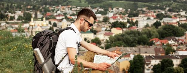 Man traveling alone reading map