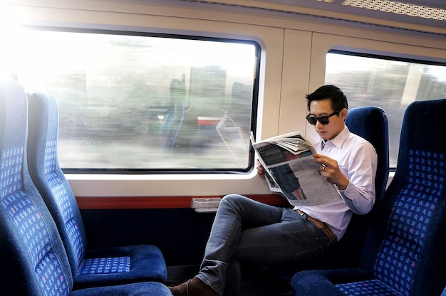 Man traveling by train and reading newspaper near the window with sunlight.
