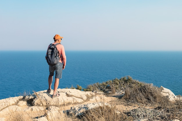 Man traveling with backpack hiking in mountains and looking on sea landscape. active healthy lifestyle adventure journey vacations.