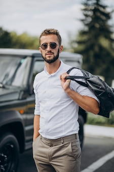 Man travelling with bag and standing by the car