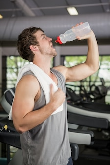 Man on treadmill drinking water at gym