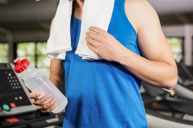 Man on treadmill holding water bottle at gym