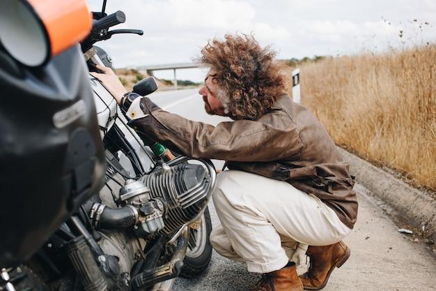 남자는 길가에 오토바이를 고치려고합니다.