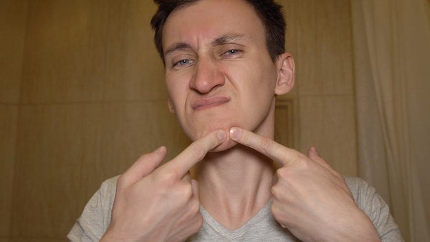 男は彼の顔ににきびを絞ろうとします。