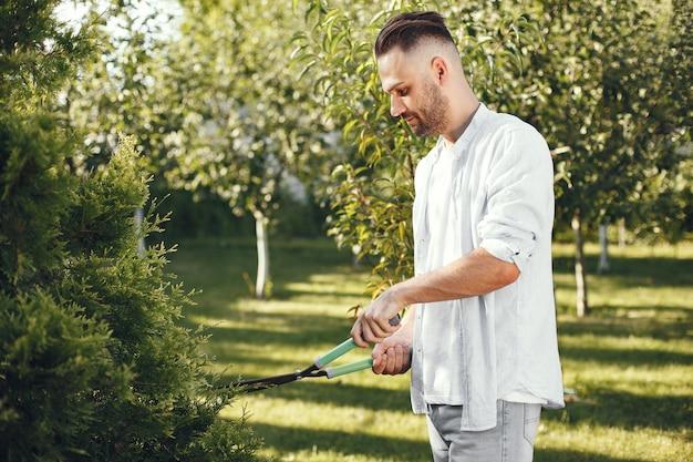 ブラシの枝をトリミングする男。男は裏庭で働いています。