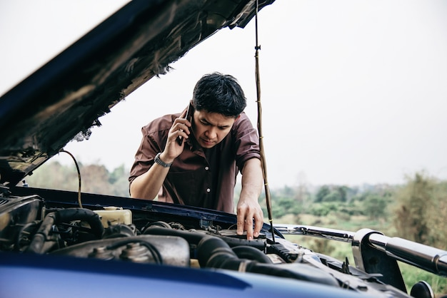 Man try to fix a car engine problem on a local road
