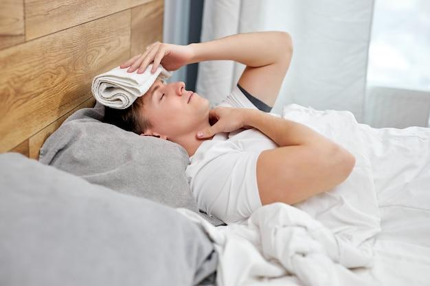 男は家で一人で熱を下げようとします。風邪の症状と原因。インフルエンザまたはコロナウイルスの病気の白人男性。男性は隔離され、喉に痛みがあります
