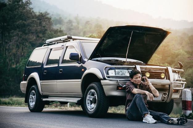 Человек пытается решить проблему с двигателем автомобиля на местной дороге