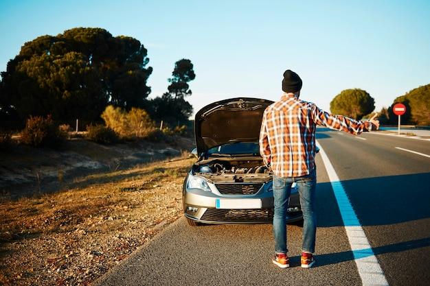Uomo che cerca di ottenere aiuto con la sua macchina rotta