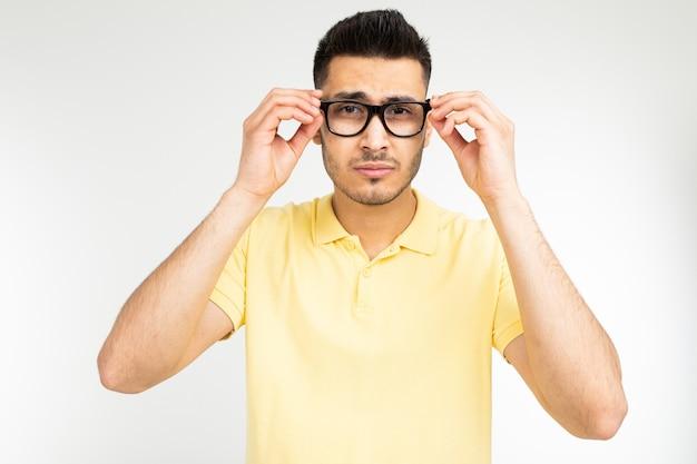 白い背景の上のビジョンのためのメガネをしようとしている男