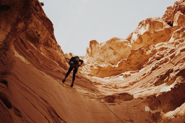 峡谷の崖を登ろうとしている男