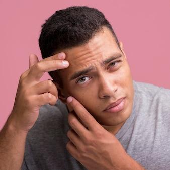 彼の顔の皮膚の欠陥を取り除こうとしている男