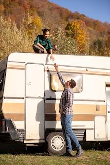 レトロなキャンピングカーの屋根に座っているガールフレンドに手を貸そうとしている男。秋の色