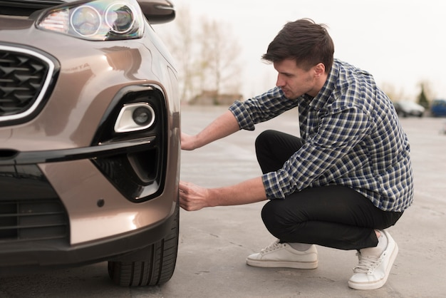 Человек пытается заменить автомобильное колесо