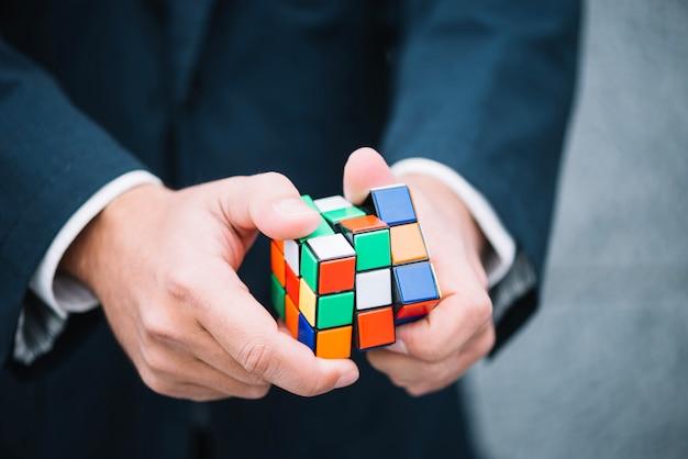Человек пытается решить кубик рубика Premium Фотографии
