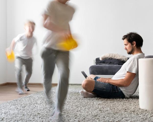 Мужчина пытается работать на ноутбуке из дома, пока ее дети бегают