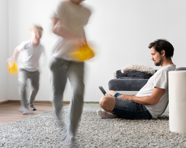 Man trying to work on laptop from home while her children are running around