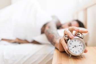 Man turning off alarm clock while lying on bed
