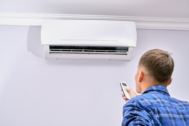 A man turns on the air conditioner with the remote control at home