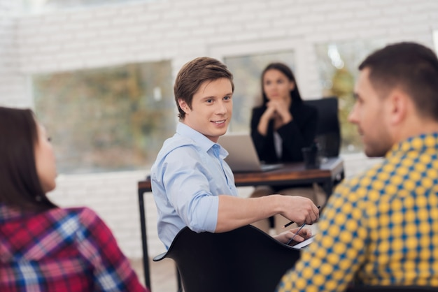 Man turns to audience of people in training sitting on chair
