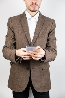 Man in tweed jacket with a mobile phone. male person in business clothing uses technology, detailed view in white background