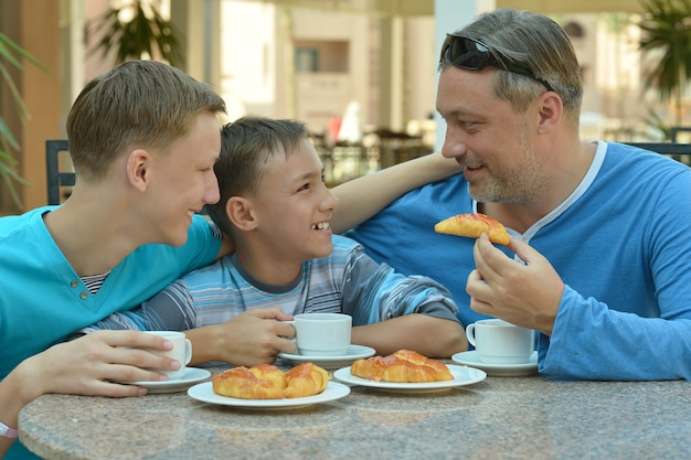 Man and two boys having breakfast on the table