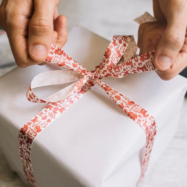 大きな贈り物の箱に弓を結んでいる男