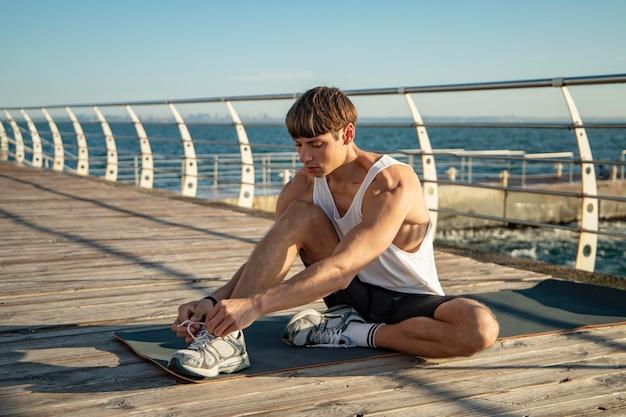 Мужчина завязывает шнурки на пляже перед тренировкой