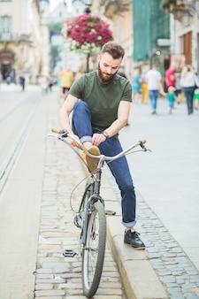 Man tying shoe before riding bicycle