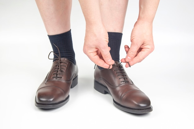 Man tying shoelaces on classic brown shoes