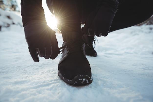 Uomo che lega i lacci delle scarpe nella foresta