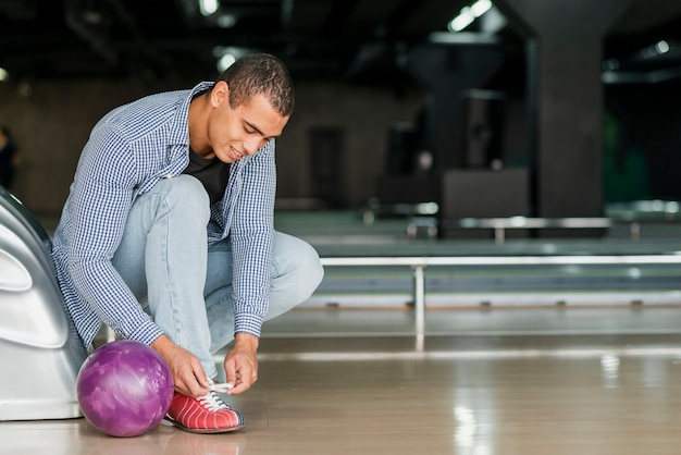 ボウリングクラブで靴ひもを結ぶ男