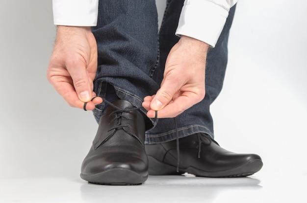 古典的な黒い靴に靴紐を結ぶ男