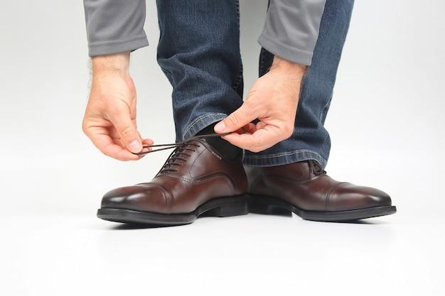 古典的な茶色のオックスフォードシューズに靴紐を結ぶ男