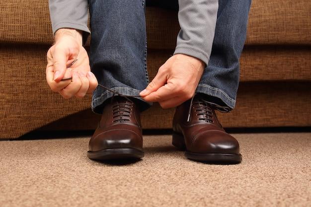 클래식 브라운 옥스포드 신발에 끈을 묶는 남자