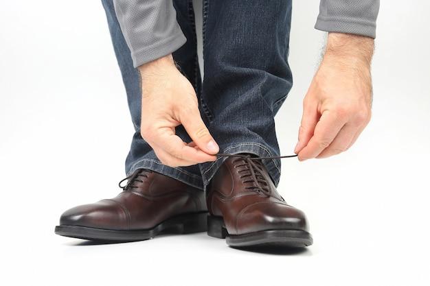 古典的な茶色の靴に靴紐を結ぶ男