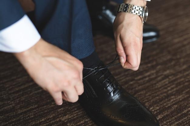 木製の床に靴ひもを結ぶ男