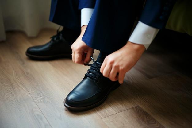 木の床の黒い靴にひもを結ぶ男