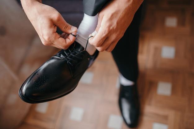 Мужчина завязывает шнурки на черных туфлях на деревянном полу