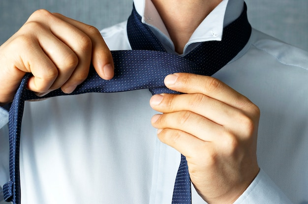 Man tying a tie close-up, concept of an office worker