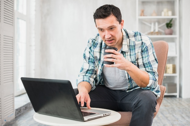 Man typing on laptop and holding cup of drink on chair