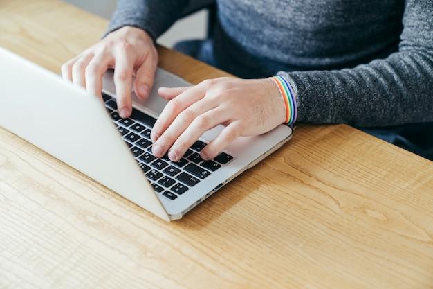 Man typing on laptop wearing rainbow gay pride bracelet