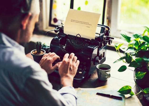 Человек, набирающий на мануальной пишущей машинке