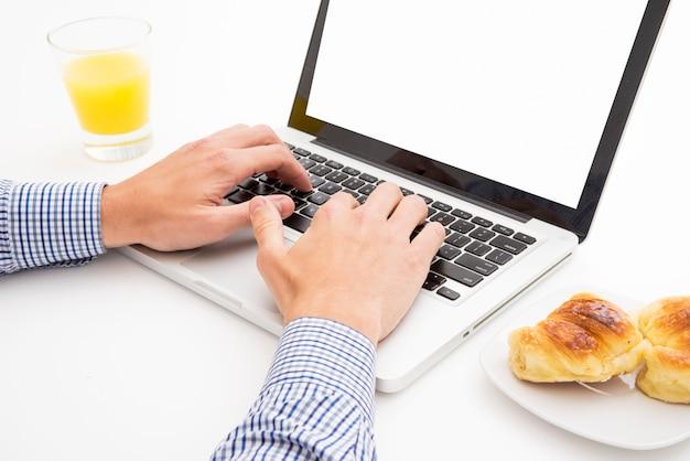 화이트 테이블 위에 아침 식사와 함께 노트북에 입력하는 남자