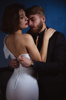 Man unbuttons the dress of his beloved woman who is gently embracing him