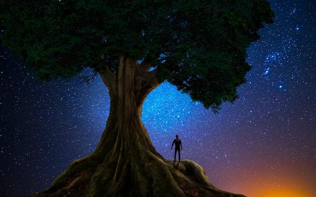 宇宙の前の木の下の男