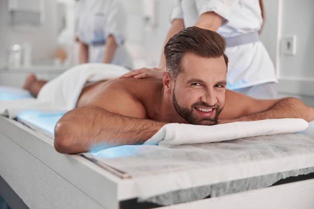 Man undergoes relaxing massage procedure with professional chiropractics lying on glowing couch