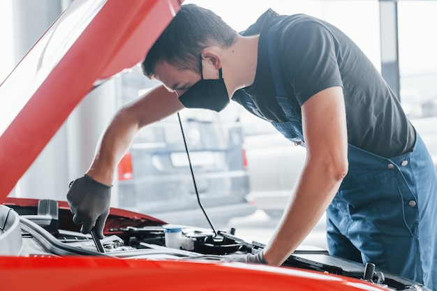 Man in uniform and black protective mask works with broken automobile. conception of car service